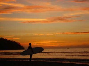 A longboard surfer watching the sunset in Guanacaste Province, in the northwest of Costa Rica.